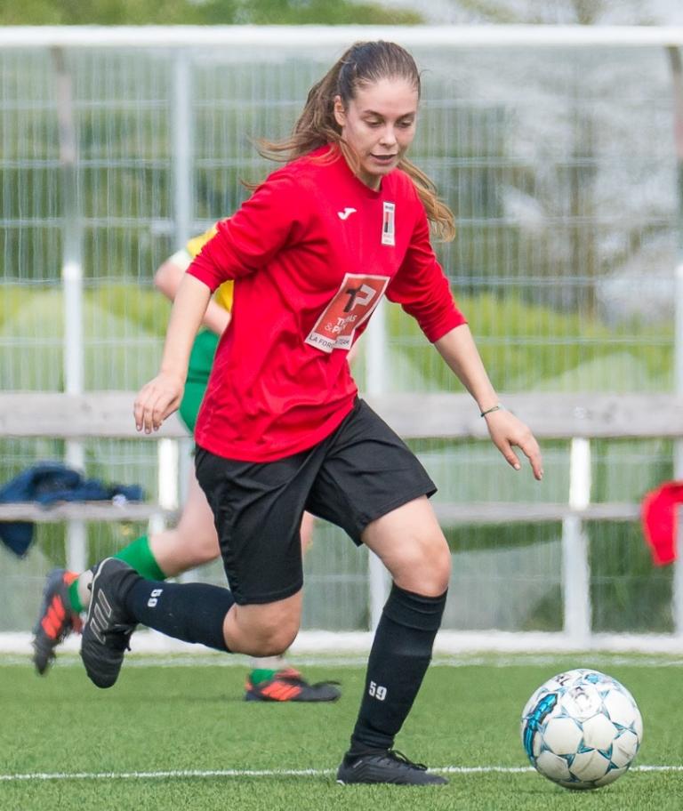 Une footbaleuse en rouge et noir derrière un ballon